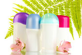 Deodorants with flowers and green leaf isolated on white — Stock Photo