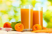 Glasses of carrot and apricot juice on white wooden table on green background — Stock Photo