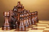 Шахматная доска с шахматной штук на коричневый фон — Стоковое фото