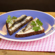 Tasty sandwiches with sprats on plate on wooden table on brown background — Stock Photo #11351910