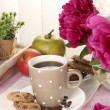 Cup of coffee, cookies, apples and flowers on table in cafe — Stock Photo