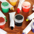 Tubes with colorful watercolors and jars with gouache on wooden table close-up — ストック写真