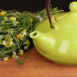 Teapot with chamomile tea on wooden table close-up — Stock Photo #11359610