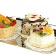 Sweet cakes with fruits and chocolate on silver tray isolated on white — Stock Photo