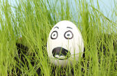 White egg with funny face in green grass — Stock Photo