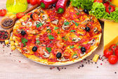 Delicious pizza and vegetables on wooden table — Stock Photo