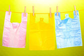 Cellophane bags hanging on rope on green background — Stock Photo
