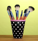 Makeup brushes in a black polka-dot cup on yellow background — Stock Photo