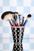 Makeup brushes in a black polka-dot cup on colorful background — Stock Photo
