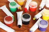 Tubes with colorful watercolors and jars with gouache on wooden table close-up — Stock Photo