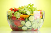 Fresh vegetable salad in transparent bowl on green background — Stock Photo