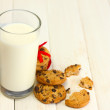 Glass of milk and chocolate chips cookies with red ribbon on wooden table — Stock Photo #11360189