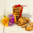 Chocolate chips cookies with red ribbon and wildflowers on wooden table — Stock Photo #11360195