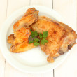 Roasted chicken wings and leg with parsley in the plate on white wooden background close-up — Stock Photo