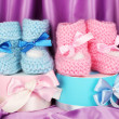 Pink and blue baby boots and gifts on silk background — Stock Photo