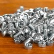 Chrome nuts and bolts on wooden background close-up - Stock Photo