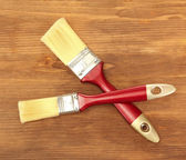 Paint brushes on wooden background — Stock Photo
