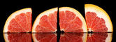 Sliced grapefruit isolated on black — Stock Photo