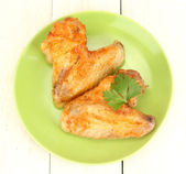 Roasted chicken wings with parsley in the plate on white wooden background close-up — Stock Photo
