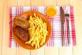 Patatas fritas con hamburguesas en la placa en primer plano de fondo de madera — Foto de Stock