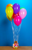 Colorful balloons holding a gift on a wooden table on a blue background — Stock Photo