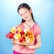 Portrait of beautiful little girl with tulips in basket on blue background — Stock Photo