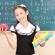 Stock Photo: Beautiful little girl in school uniform with books and apple in class room