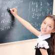 Stock Photo: Beautiful little girl writing on classroom board