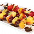 Mixed fruits and berries on skewers with chocolate isolated on white — Stock Photo #11402262