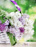 Beautiful lilac flowers in basket on wooden table on green background — Stock Photo