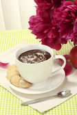 Cup hot chocolate, apple, cookies and flowers on table in cafe — Stock Photo