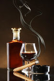 Bottle and glass of brandy and cigar on brown background — Stock Photo