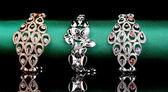 Três pulseiras elegantes sobre o pano verde sobre fundo preto — Foto Stock