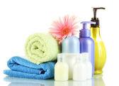 Bouteilles cosmétiques serviettes et fleur isolé sur blanc — Photo