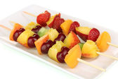Mixed fruits and berries on skewers isolated on white — Stock Photo