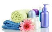 Cosmetics bottles with towels and flower isolated on white — Foto Stock