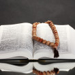 Russian open holy bible with wooden rosary on black backround - Stock Photo