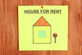 Poster about renting the house with the key on wooden background close-up — Stock Photo