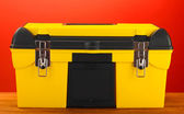 Yellow tool box on red background close-up — Stock Photo