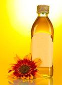Olio di girasole e semi di girasole su sfondo giallo — Foto Stock