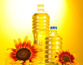 Sunflower oil and sunflowers on yellow background — Stock Photo