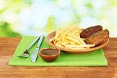 Patatas fritas con hamburguesas en la placa en primer plano de fondo verde — Foto de Stock