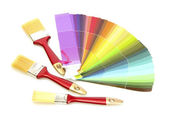Paint brushes and bright palette of colors isolated on white — Stock Photo