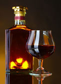 Glass of brandy and bottle on brown background — Stock Photo