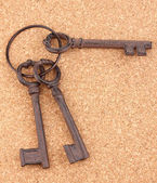A bunch of antique keys on cork background — Stock Photo