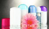 Botttles desodorante con flores sobre fondo gris — Foto de Stock