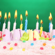 Birthday cake with candles on green background — Stock Photo