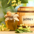 Jar and barrel with linden honey and flowers on wooden table on green background — Stock Photo #11466459