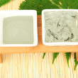 Cosmetic clay for spa treatments on straw background close-up - Stock Photo