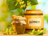 Jar and barrel with linden honey and flowers on wooden table on green background — Stock Photo
